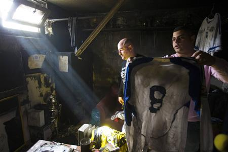 Employee of Beitar Jerusalem holds up a shirt that was damaged along with other items in a suspected arson attack in Jerusalem